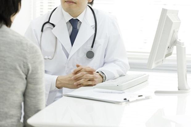 患者の症状を聞く医師